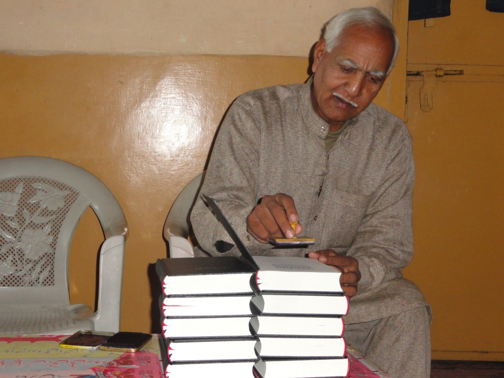 Urdu Bible Distribution Program. Mr. Arif is stamping the Bibles as a gift from Calvary Chapel Pakistan before presenting them.