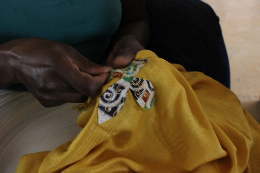 Women sew on shapes then sew sequence around them.